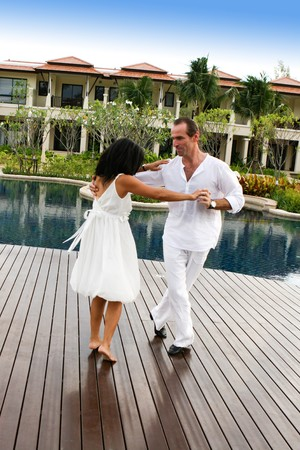 Attractive multi-cultural couple dancing by the swimming pool.