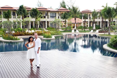 interracial family: Attractive multi-cultural couple by the swimming pool. Editorial