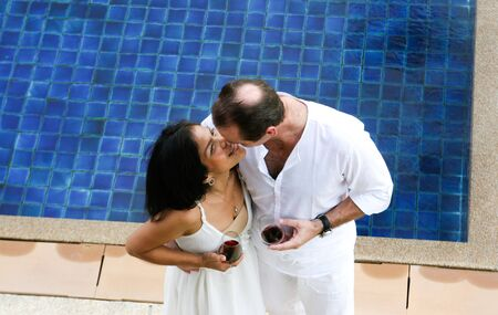 Attractive multicultural couple enjoying red wine by the swimming pool. photo