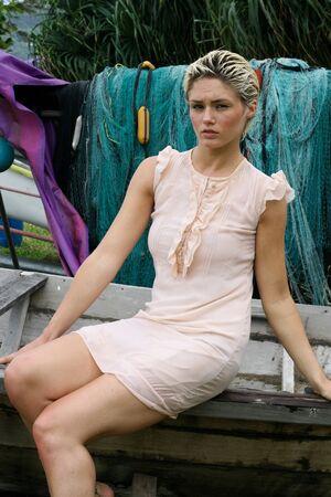 Beautiful blond woman sitting on a fishing boat. photo