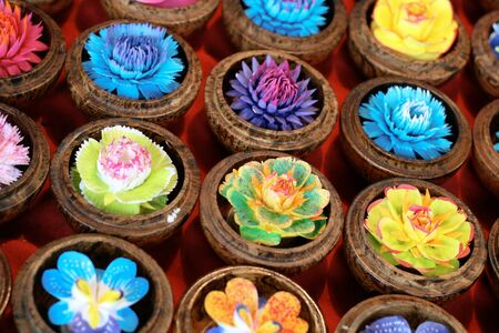 homeware: Close-up of pretty flower candles in wooden boxes.