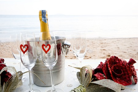 Chilled champagne and wine glasses on a table at the beach. photo