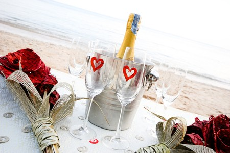 destination scenic: Chilled champagne and wine glasses on a table at the beach.