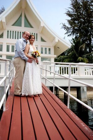 Happy bride and groom outside a wedding chapel. Stock Photo - 4444897