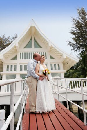 Happy bride and groom outside a wedding chapel. Stock Photo - 4444895