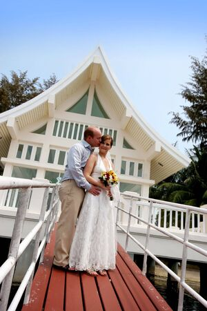 Happy bride and groom outside a wedding chapel. Stock Photo - 4444893