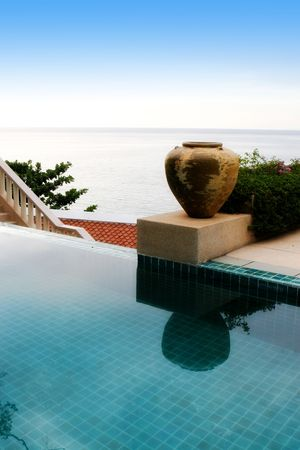 overlooking: Tropical swimming pool overlooking views of the ocean.