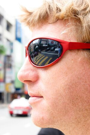 Close-up of a man crossing the road in the city. Pedestrian crossing reflection in his sunglasses. Stock Photo - 4627968