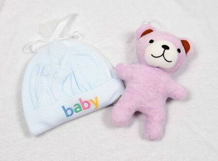 Baby hat and booties with a toy bear on white toweling fabric.
