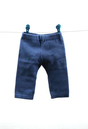 baby wardrobe: Pair of blue babys pants hanging on a clothes line - isolated. Stock Photo
