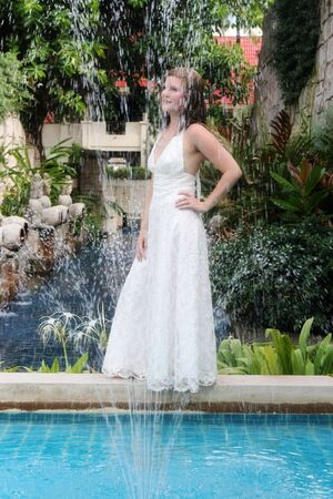 trash the dress: Beautiful bride standing by a water fountain.