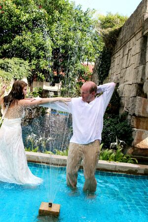 trash the dress: Gorgeous bride and groom dancing in the water during a trash the dress photo shoot. Stock Photo