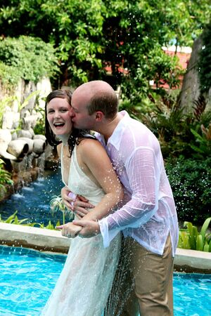 Gorgeous bride and groom standing by a water fountain. photo