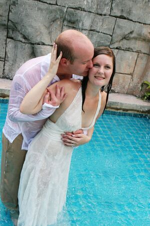 Gorgeous bride and groom playing in the water during a trash the dress photo shoot. Stock Photo - 4665318