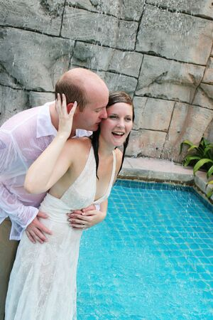 Gorgeous bride and groom playing in the water during a trash the dress photo shoot. Stock Photo - 4665322