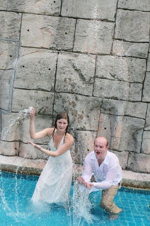 Gorgeous bride and groom playing in the water during a trash the dress photo shoot.