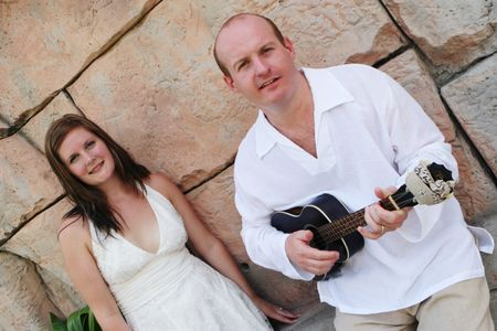Groom playing the guitar to his new bride. Stock Photo - 4665316