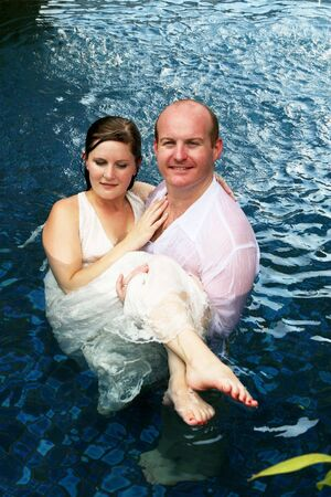 Gorgeous bride and groom in the water during a trash the dress photo shoot. photo