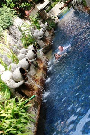 Couple swimming under Thai statues overlooking a swimming pool area - travel and tourism. photo