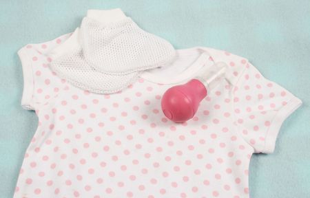 mucous: Pink polka dot baby outfit with a aspirator. Stock Photo