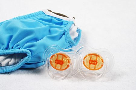 togs: Babys first swimsuit with pacifiers. Stock Photo