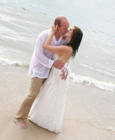 Attractive young bride and groom on the beach. Stock Photo - 4780303