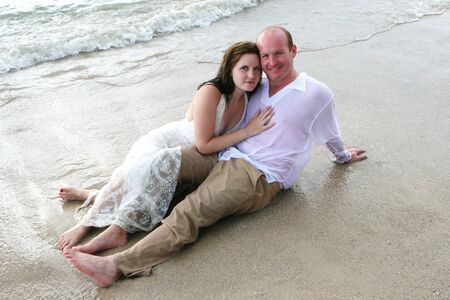 trash the dress: Attractive young bride and groom on the beach. Stock Photo