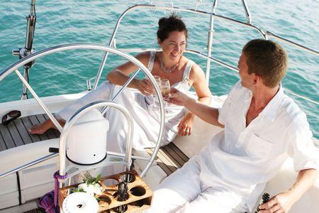 beach cruiser: Happy bride and groom on a luxury yacht.
