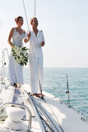 destinations: Happy bride and groom on a luxury yacht.