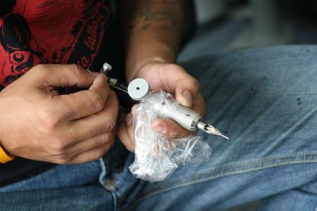 Close-up of a tattoo artist holding a needle gun. photo