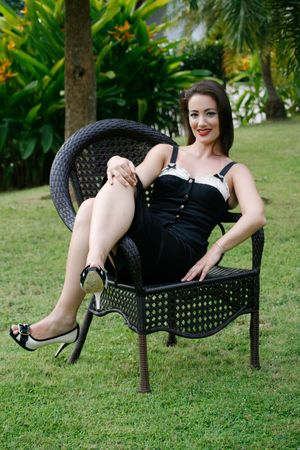 Gorgeous woman sitting on a chair - retro pin-up girl style. Stock Photo - 4911875