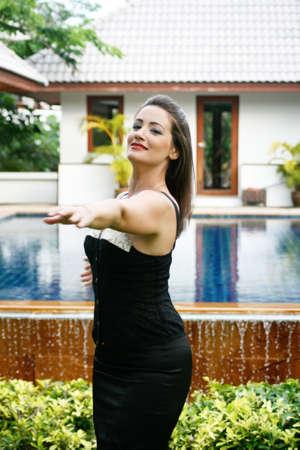 Beautiful woman dancing by the swimming pool.