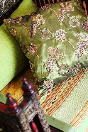 Close-up of a green oriental silk cushion on a sofa. photo