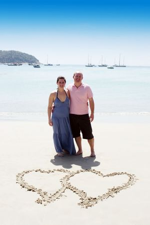 Happy couple on the beach with a heart in the sand. photo