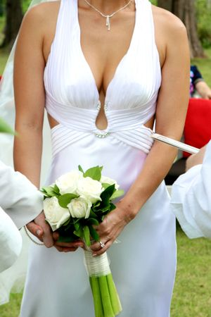 Beautiful bride holding a wedding bouquet of white roses. photo