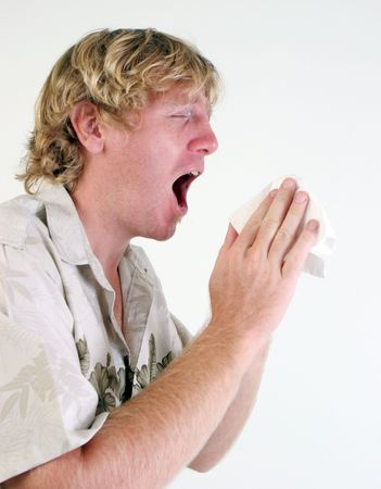 swine flu vaccine: Young man with a cold or flu sneezing - isolated.