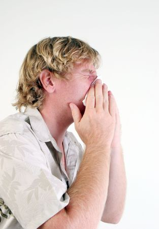 Young man with a cold or flu sneezing - isolated. Stock Photo - 5899696