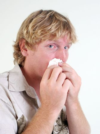Young man with a cold or flu sneezing - isolated. Stock Photo - 5899699