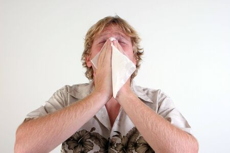 Young man with a cold or flu sneezing - isolated. Stock Photo - 5899698