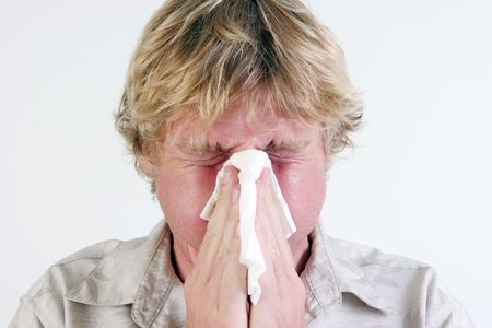Young man with a cold or flu sneezing - isolated. Stock Photo - 5899706