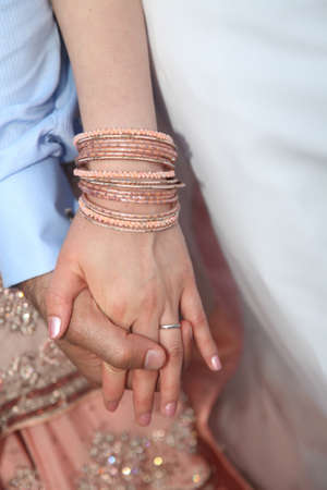 pakistani pakistan: Close-up of a bride and groom holding hands - Pakistani wedding.
