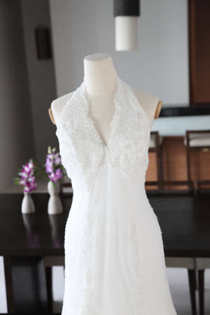 Beautiful white silk and satin wedding dress hanging on a mannequin. photo