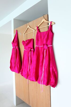 Bright pink bridesmaids dresses hanging up. photo
