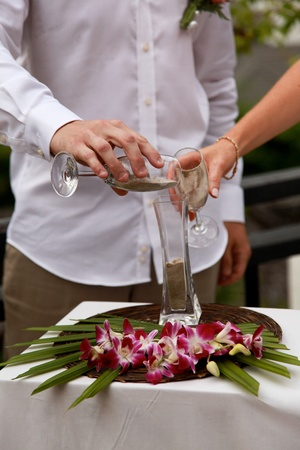 Close-up of a bride and groom during a sand pouring ceremony  photo