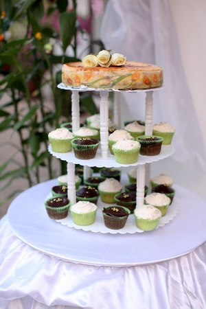 Wedding cake with cup cake style on a 3-tiered tray  photo