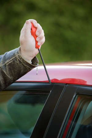 perpetrator: Burglar breaks into a car Stock Photo