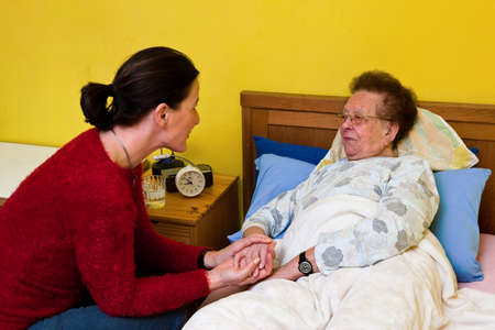 nursing association: Sick senior is visited by daughter Stock Photo