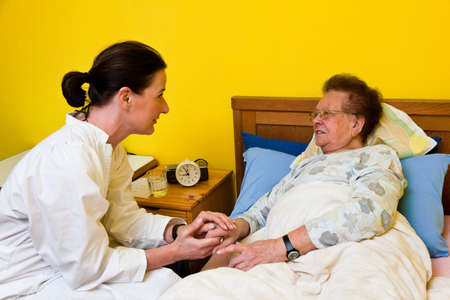 the elderly tutor: Sick senior is visited by daughter Stock Photo