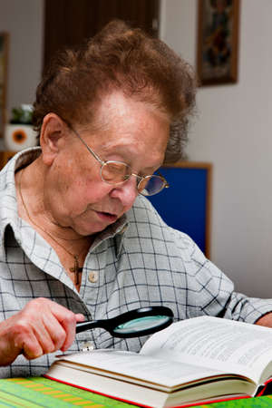 impaired: Old Woman with glasses reading a book