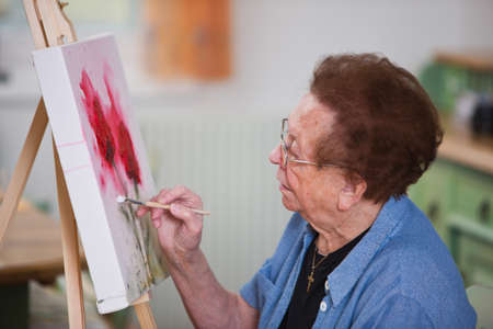 Old woman paints a picture Stock Photo